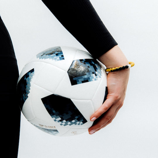 A hand wearing a gold and black swirl silicone beaded bracelet holding a soccer ball.
