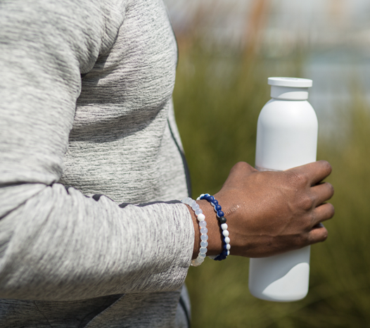 Male wearing a navy and white silicone beaded bracelet on wrist while holding a water bottle.