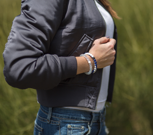 Woman wearing a gray bomber jacket with a navy and white silicone beaded bracelet on wrist.