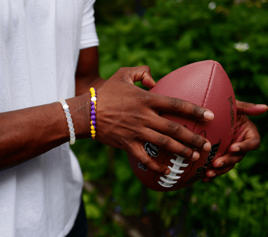 Man holding a football wearing a yellow and purple silicone beaded bracelet.