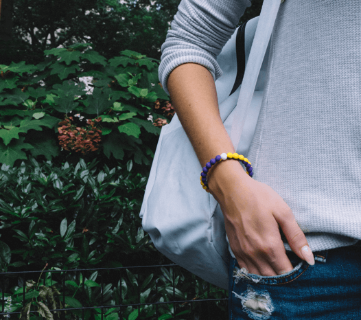 Woman with hands in her pocket wearing a yellow and purple silicone beaded bracelet.