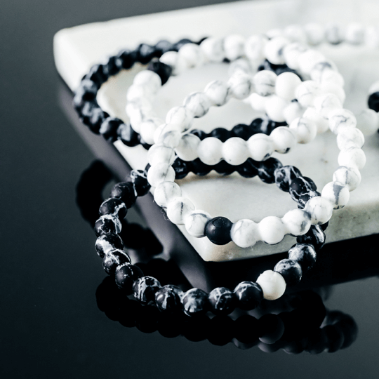 Pile of black and white marble silicone beaded bracelets on marble slab on top of black reflective surface.
