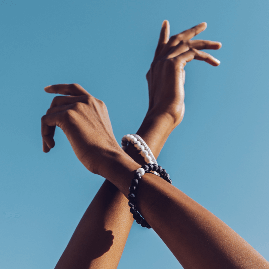 Female with hands crossed in the air wearing black and white marble silicone beaded bracelets.