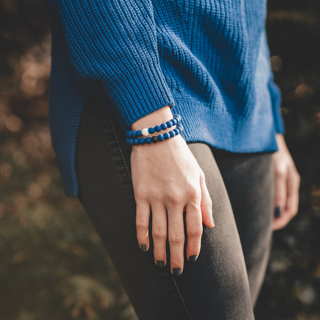 Women wearing two blue silicone beaded bracelets on wrist.