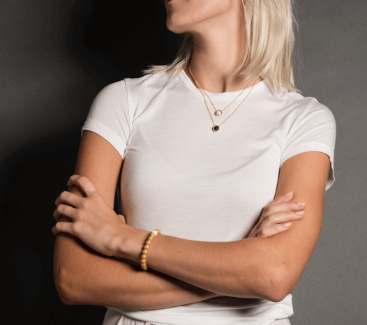 Female in white t-shirt wearing gold metallic silicone beaded bracelet on wrist with arms crossed.