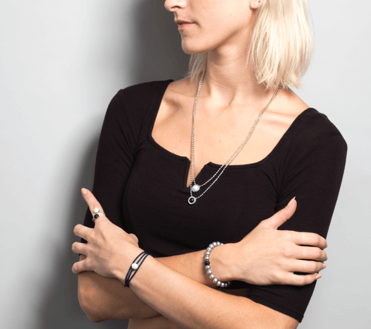 Female in black t-shirt wearing silver metallic silicone beaded bracelet on wrist with arms crossed.