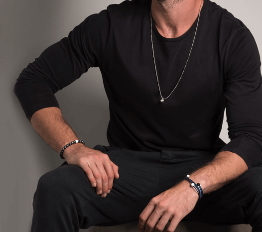 Male in all black wearing gunmetal metallic silicone beaded bracelet on wrist with hand on knee.