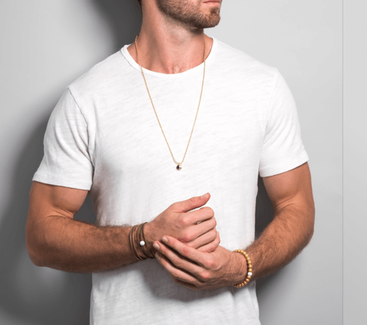 Male in white t-shirt wearing gold metallic silicone beaded bracelet on wrist while holding hands together.