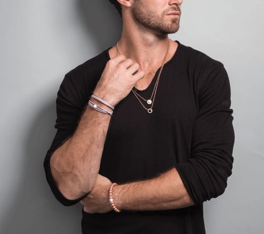 Male in black shirt wearing rose gold metallic silicone beaded bracelet.
