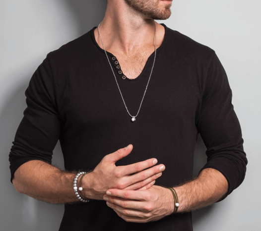 Male in black shirt wearing silver metallic silicone beaded bracelet while holding hands together.