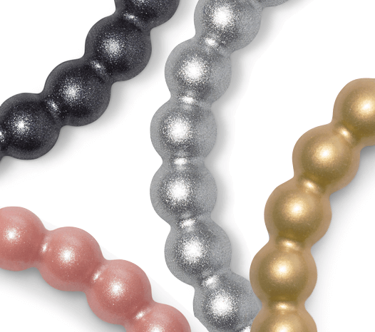 Close up of gunmetal, rose gold, silver, and gold metallic silicone beaded bracelets.