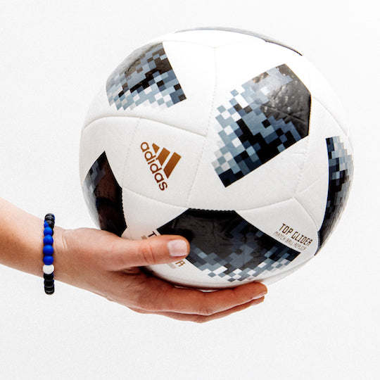 A wearing a blue and black swirl silicone beaded bracelet holding a soccer ball.