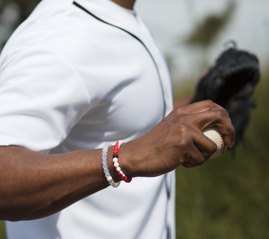 Male wearing red and white silicone beaded bracelet on wrist while holding a baseball.