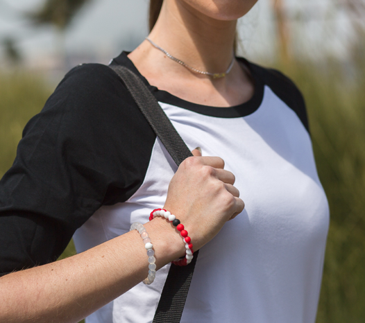 Woman wearing red and white silicone beaded bracelet on wrist while holding shoulder bag strap.