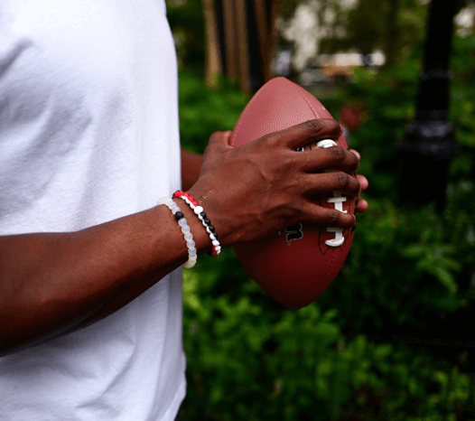 Man holding a football wearing a white, black, red and white silicone beaded bracelet.
