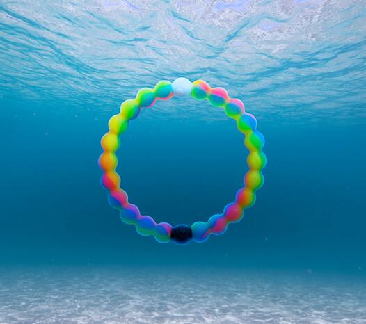 Neon rainbow swirl silicone beaded bracelet under water.