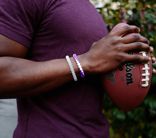 Man holding football wearing a purple and white silicone beaded bracelet.