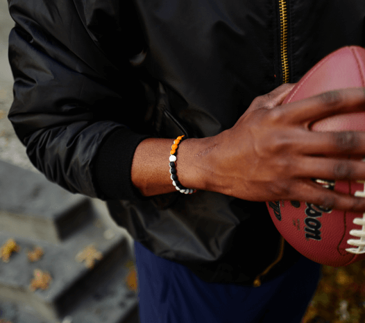 Man holding a football wearing an orange, black and gray silicone beaded bracelet.