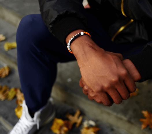 Man holding his wrist wearing an orange, black and gray silicone beaded bracelet.