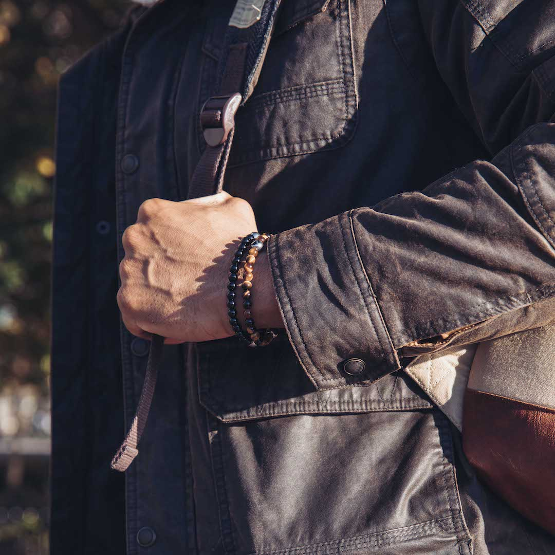 Male in brown jacket wearing black stone bracelet and brown stone bracelet on wrist.