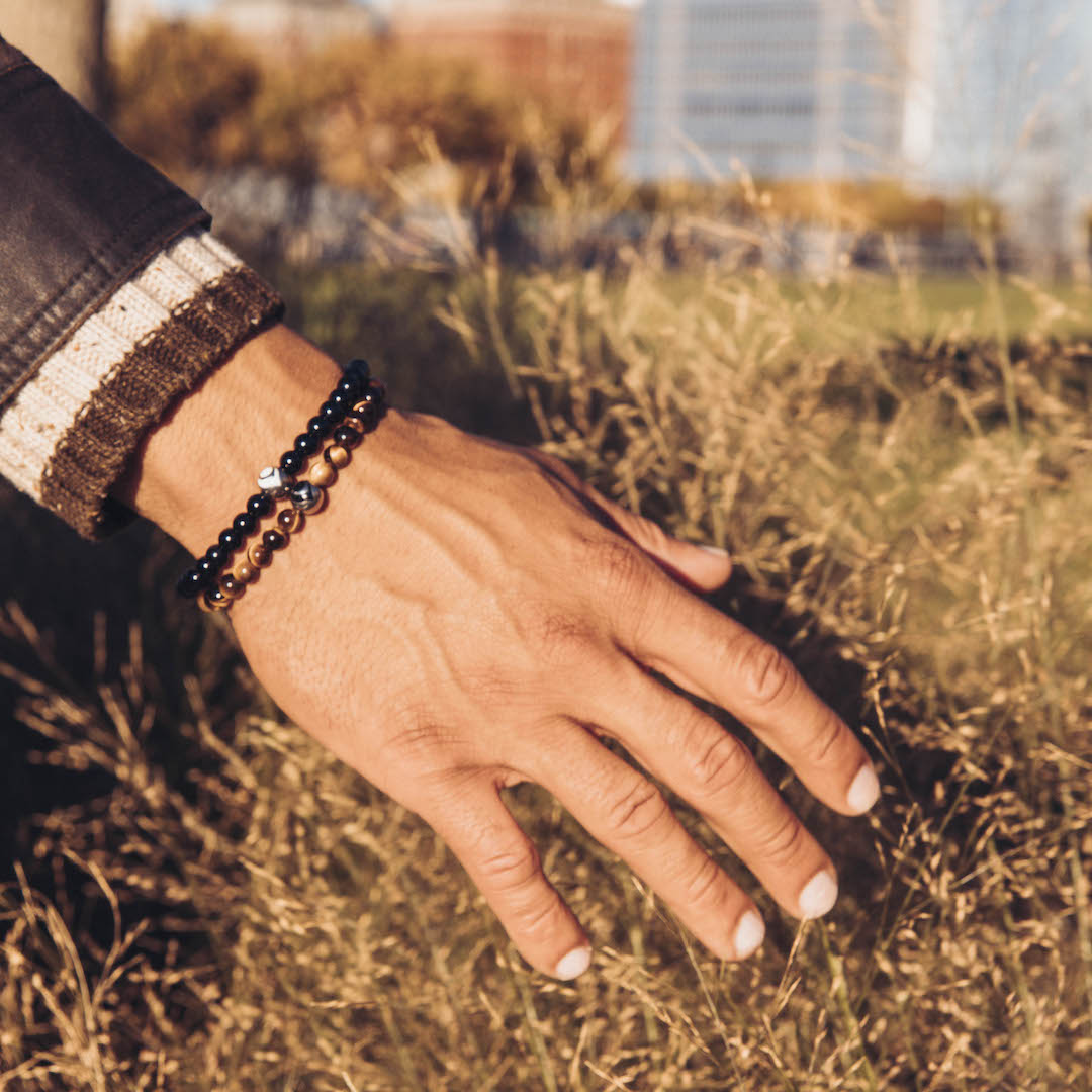 Close up of male wearing black stone bracelet and brown stone bracelet on wrist while touching tall grass.