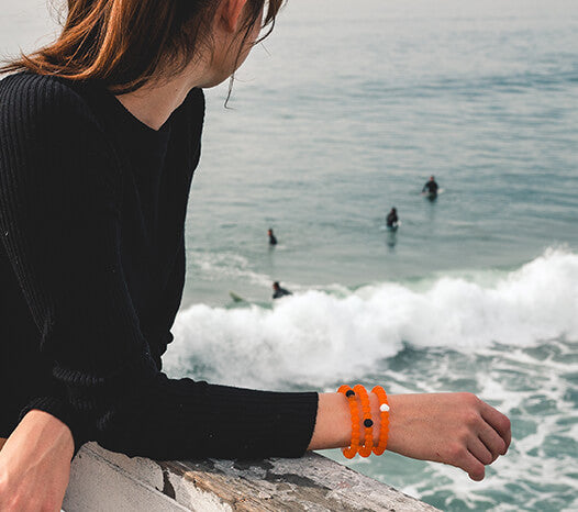 Female wearing orange silicone beaded bracelets on wrist while leaning on balcony looking at ocean.