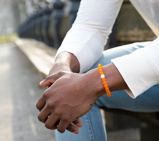 Male sitting on a bench wearing an orange silicone beaded bracelet on wrist.