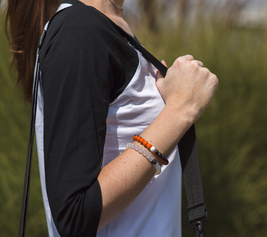 Woman wearing orange and black silicone beaded bracelet on wrist while holding shoulder bag straps.