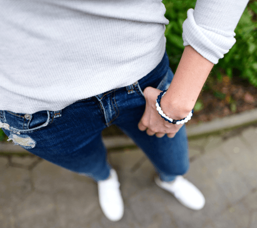 A person with their hand in their pocket wearing a white and navy blue silicone beaded bracelet.