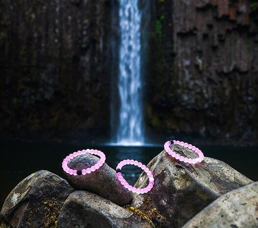 Three light pink silicone beaded bracelets sitting on rocks with a waterfall in the background.