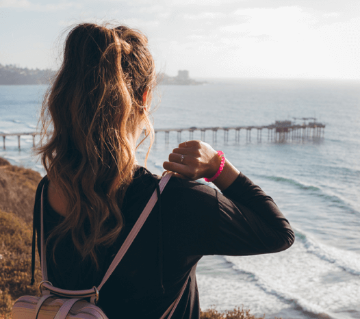 Girl wearing pink silicone beaded bracelet on wrist while looking at a pier.
