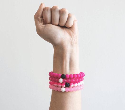 Close up of a fist with stack of hot pink, pink, pink swirl, and light pink silicone beaded bracelets on wrist.