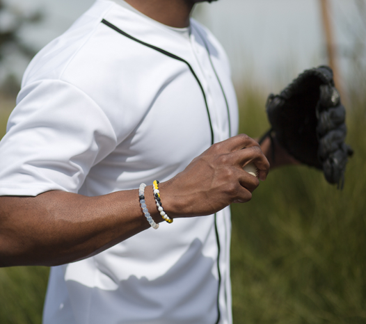 Male wearing black, white and yellow silicone beaded bracelet on wrist while holding a baseball.