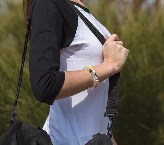 Woman wearing black, white and yellow silicone beaded bracelet on wrist while holding shoulder bag strap.