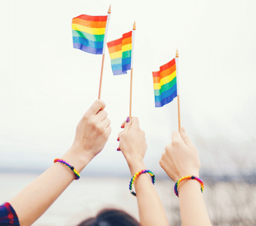Three people holding rainbow flags with rainbow swirl silicone beaded bracelets on their wrists.
