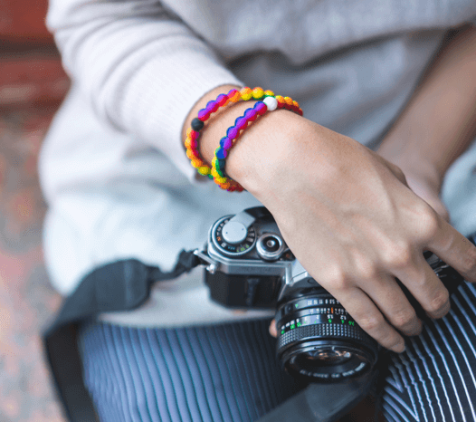 Woman holding camera in her lap wearing a rainbow swirl silicone beaded bracelet.