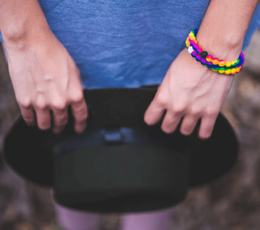 Woman holding black hat and wearing two rainbow swirl silicone beaded bracelets on her wrist.