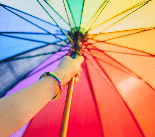 Person holding rainbow umbrella and wearing a rainbow swirl silicone beaded bracelet on their wrist.