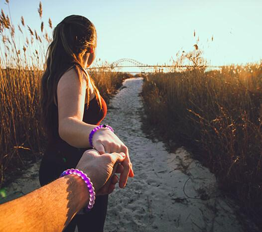 Male and female holding hands and wearing purple silicone beaded bracelets on wrist while woman is leading male towards beach.
