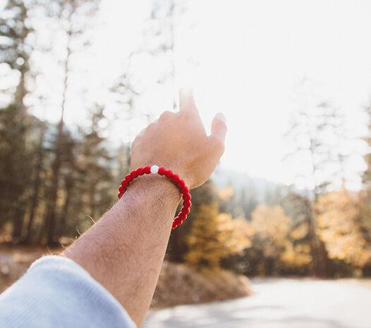 Male wearing red silicone beaded bracelet on wrist while reaching toward the sun with a forest in the background.