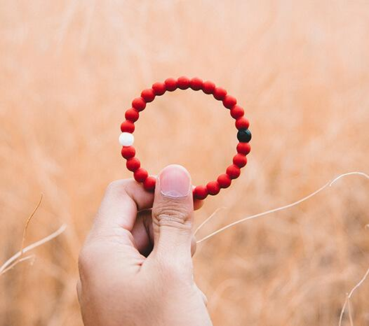 Close up of hand holding red silicone beaded bracelet.