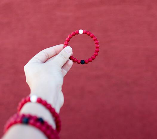 Close up of hand holding red silicone beaded bracelet while wearing a stack of red silicone beaded bracelets on wrist.