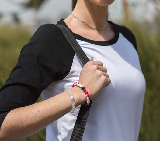 Woman wearing red and white silicone beaded bracelet on wrist while holding shoulder bag straps.