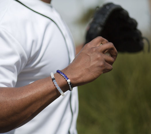 Male wearing black, white and purple silicone beaded bracelet on wrist while holding a baseball.