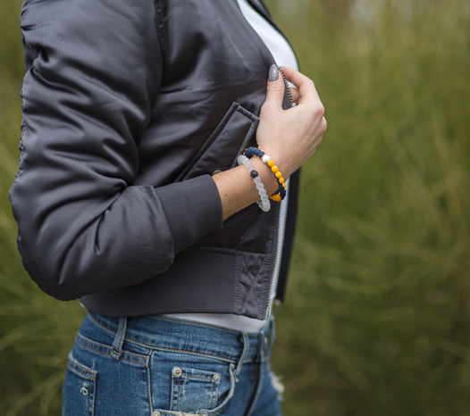 Woman wearing a gray bomber jacket with a gold and navy silicone beaded bracelet on wrist.