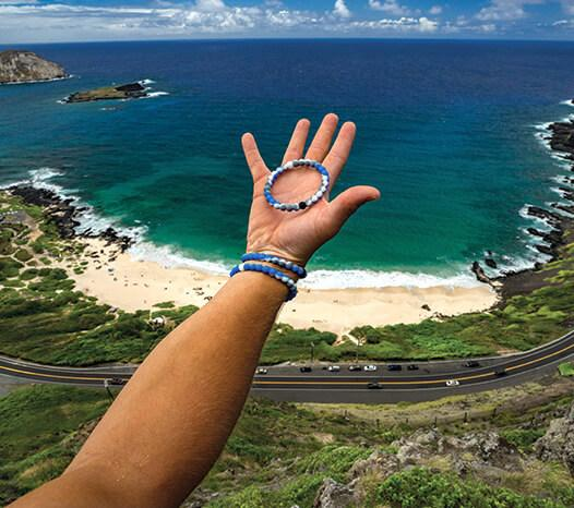 Arm with blue, gray and white swirl silicone beaded bracelets on wrist with coastline in the background.