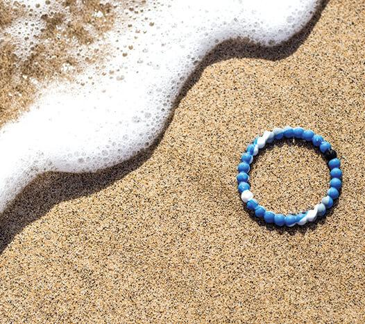Blue, white and gray swirl silicone beaded bracelet in sand next to sea foam.