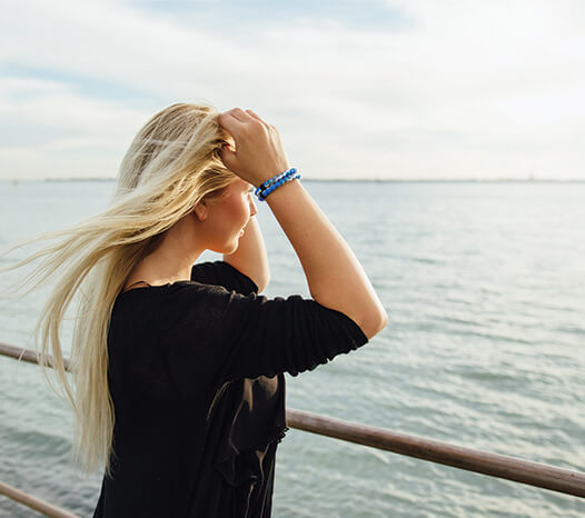 Blonde female wearing blue, white and gray swirl silicone beaded bracelets while touching hair and looking at the ocean.