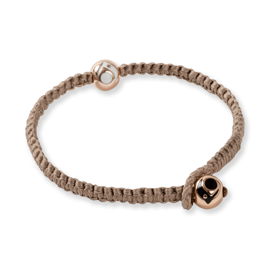 Side angle of taupe woven bracelet with two rose gold metal beads.