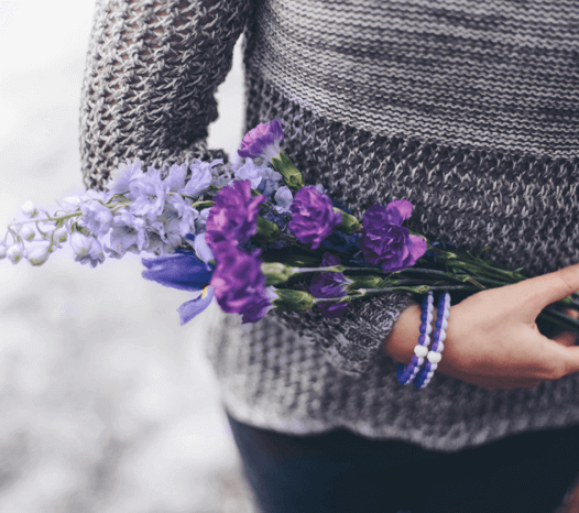 Woman wearing two purple silicone beaded bracelets on wrist while holding bouquet of purple flowers.